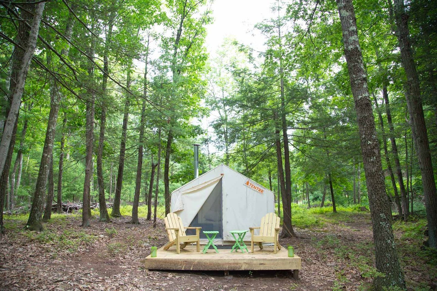 Tentrr tent and Adirondack chairs in the woods.