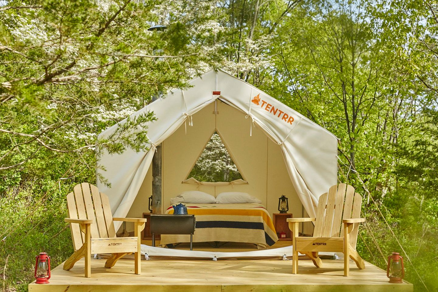 Tentrr tent with queen bed and Adirondack chairs in the woods.