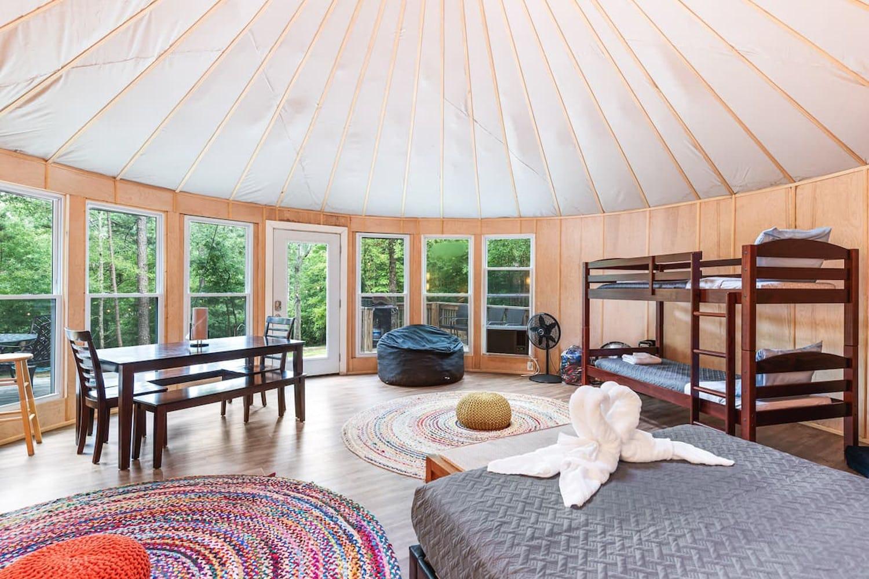 Luxurious glamping yurt with panoramic windows and circular rugs.
