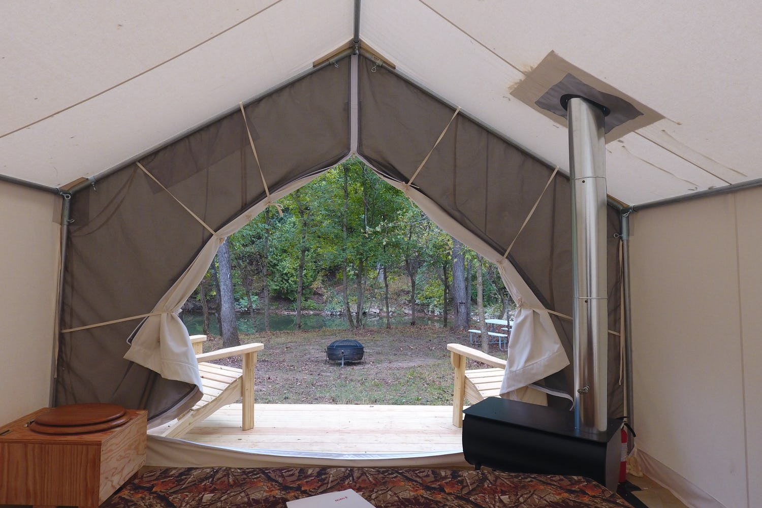 View of campsite from interior of canvas glamping tent of a campsite with a wood stove in Virginia.
