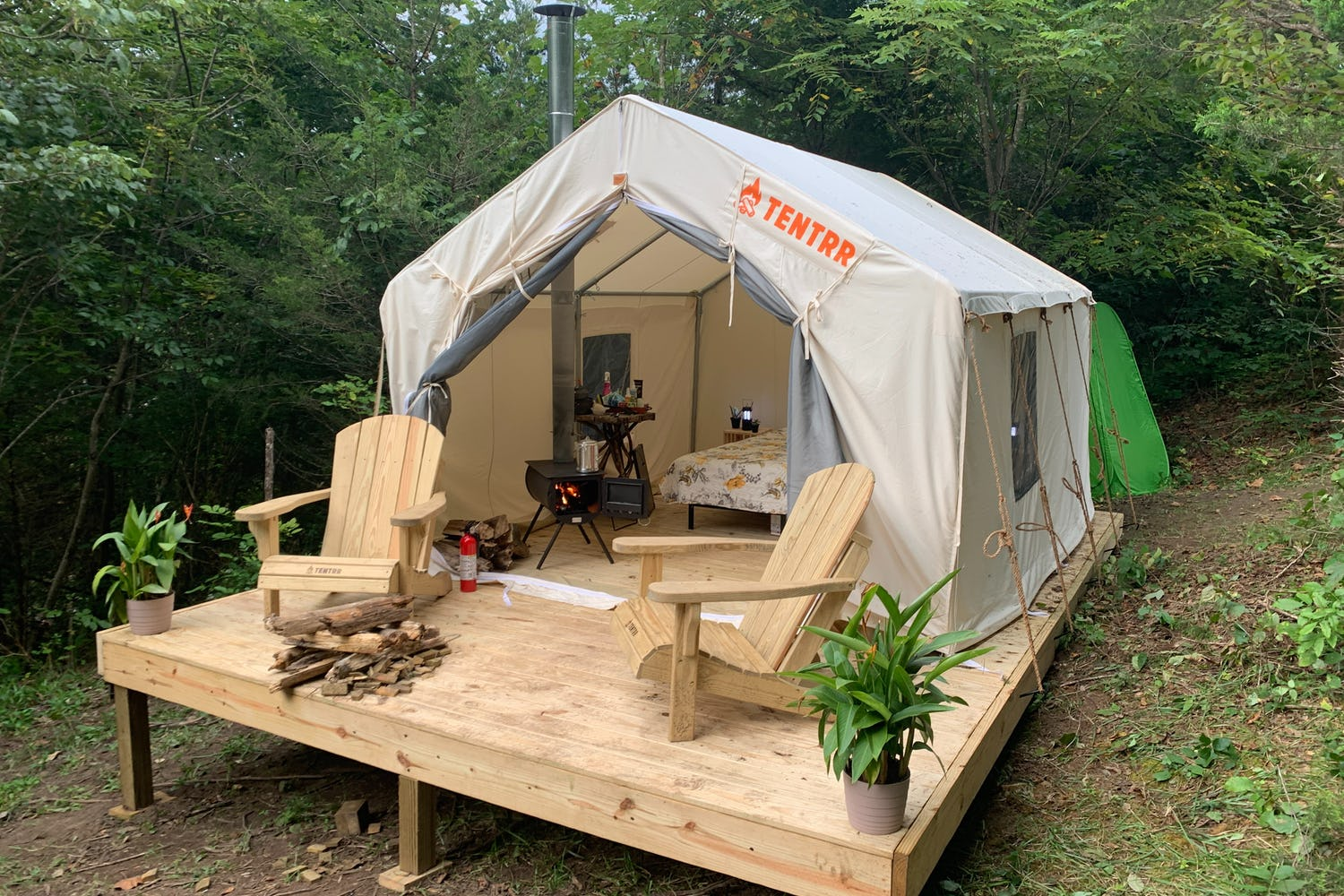 Tentrr canvas glamping platform tent with wood stove and adirondack chairs at a campsite in Virginia.
