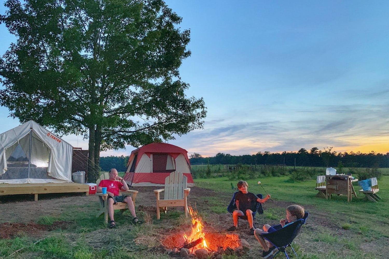 Family sitting around a fire roasting marshmallows.