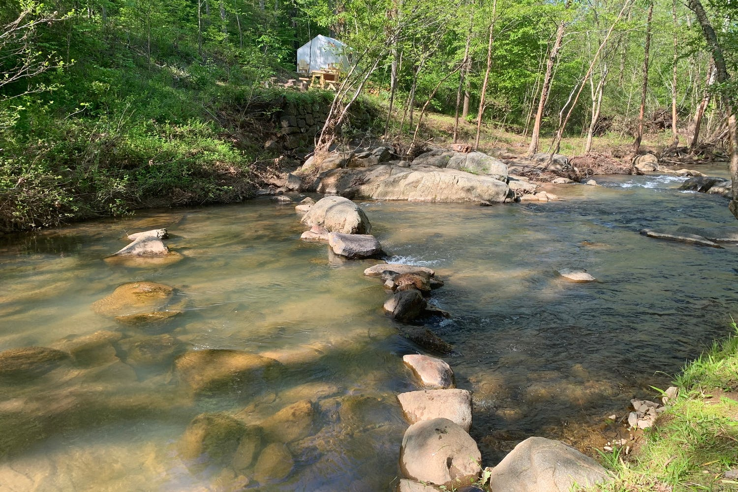Glamping site beside flowing river with rock path across in Virginia.